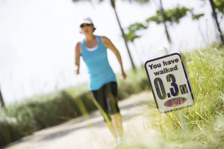 Rear view of woman power walking past mile marker.